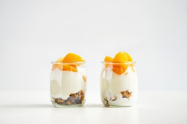 Frascos simetricamente localizados de iogurte grego com granola e damascos enlatados