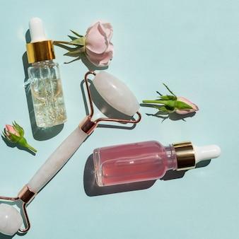 Frascos transparentes com soro de beleza, ácido hialurônico, ouro 24k e água de rosas sobre fundo azul com rolo massageador de quartzo. conceito luxuoso do tratamento do rosto e do corpo em casa.