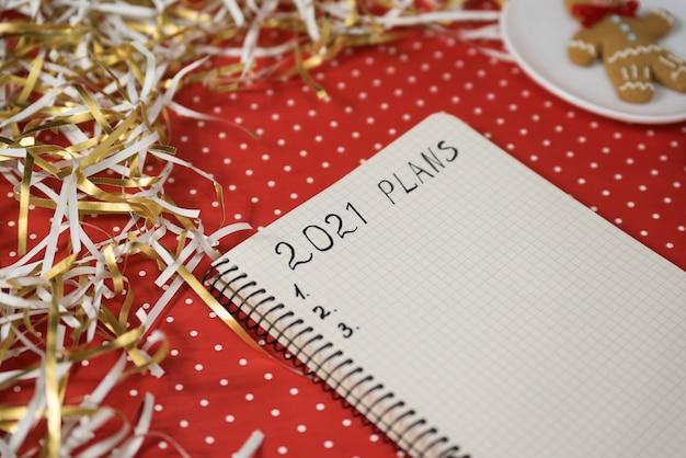Frase 2021 planos em um caderno. homem-biscoito sobre fundo vermelho, enfeites de natal. conceito de ano novo.