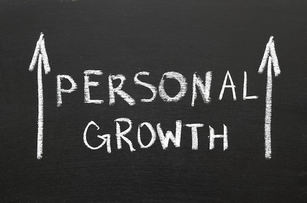 Frase de crescimento pessoal escrita à mão no quadro-negro com setas ascendentes