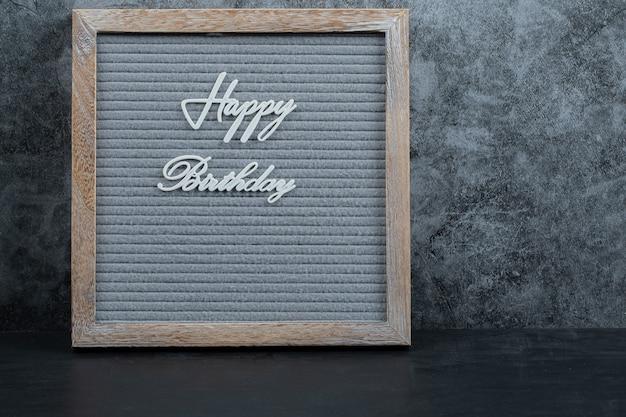 Frase de feliz aniversário embutida no tecido cinza