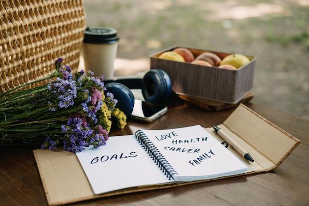 Frase motivacional de objetivos de resoluções de ano novo em caderno aberto sobre a mesa ao ar livre natureza morta