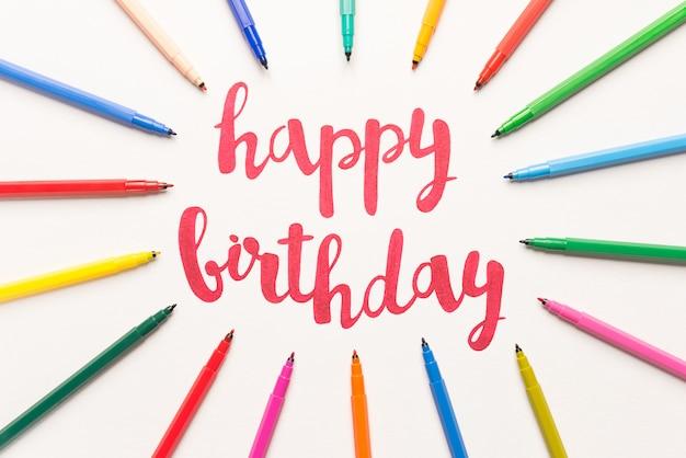 Frase motivacional 'feliz aniversário' para cartões e cartazes desenhando com marcador vermelho sobre papel branco. letras em papel entre marcadores coloridos