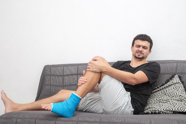 Fratura óssea em pé e perna em paciente masculino e recuperação ortopédica deitado no sofá, permanecendo no tornozelo com tala azul
