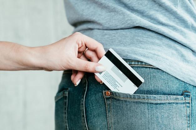 Fraude bancária. perigos do gerenciamento de dinheiro eletrônico. roubo de cartão de crédito online. mão roubando o cartão do banco do bolso do homem.