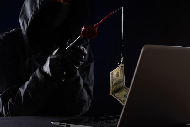 Fraude na internet usando tecnologia de computador, roubo de dinheiro na internet, roubo de dados de cartão de crédito. hacker pegou uma nota de um dólar de dinheiro na isca.