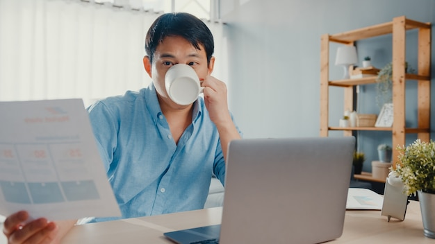 Freelance ásia cara casual wear usando laptop e beber café na sala de estar em casa.