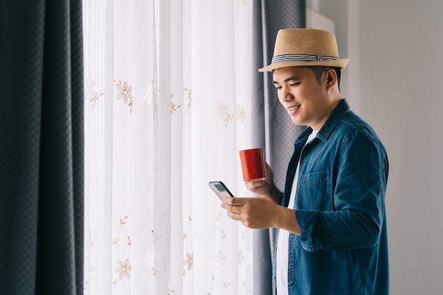 Freelance asiático bebendo café e use seu telefone para jogar nas redes sociais perto da janela na hora do café.