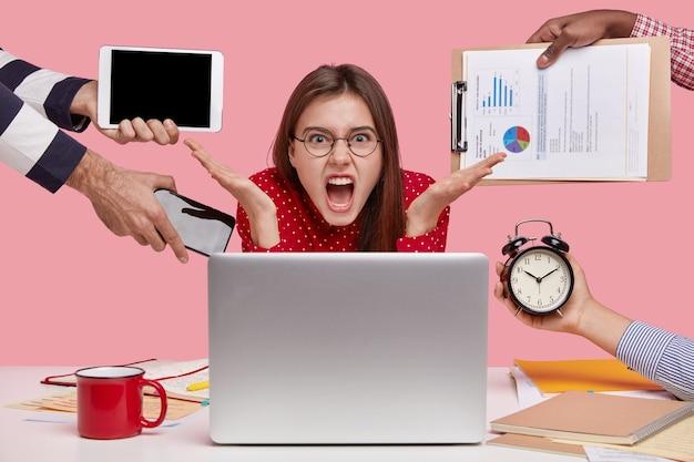 Freelancer aborrecido gesticula em frente ao laptop, tem muita papelada, faz hora extra, chora desesperadamente
