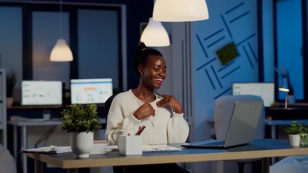 Freelancer africano feliz recebendo boas notícias no laptop trabalhando hora extra no escritório da empresa iniciante