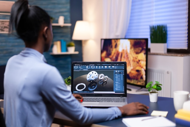 Freelancer africano usando cad para projetar um conceito técnico do escritório em casa à noite. engenheira industrial negra estudando ideia de protótipo em computador pessoal mostrando software no dispositivo dis