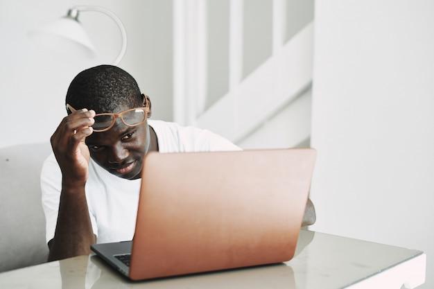Freelancer americano africano masculino com laptop em casa