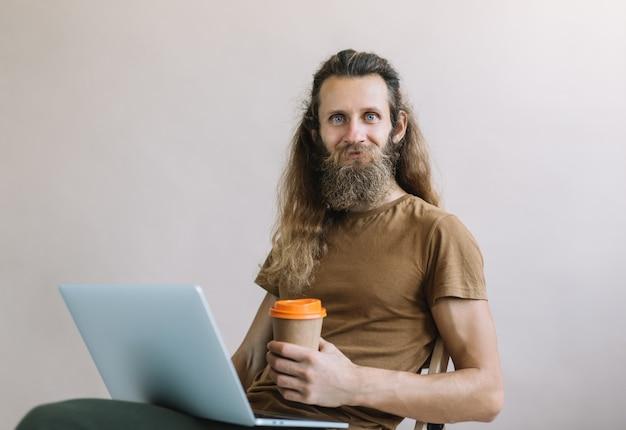 Freelancer barbudo usando laptop, tomando café, trabalhando em casa