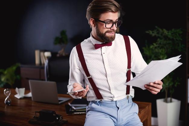 Freelancer bonito lendo documentos no escritório doméstico
