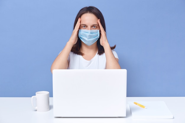 Freelancer cansado trabalhando no colo, mantendo as mãos na cabeça, tem muito trabalho, garota exausta posando isolado em azul. conceito de trabalho distante.