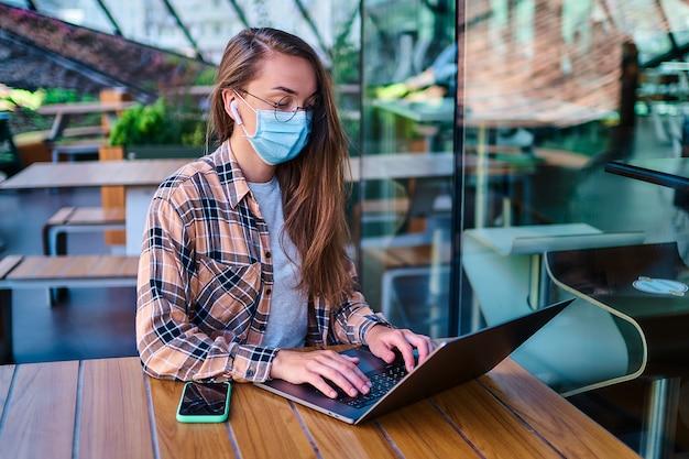 Freelancer casual mulher trabalhadora em máscara protetora, fones de ouvido sem fio brancos e óculos funciona on-line no computador no café. distância social e assistência médica em locais públicos