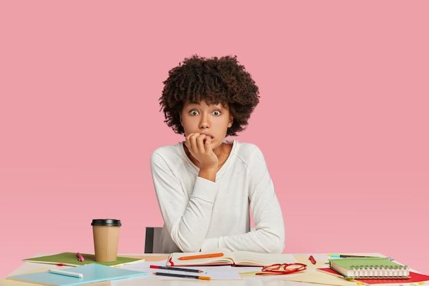 Freelancer chocado de pele escura morde as unhas nervosamente, tem prazo para terminar o trabalho, senta-se na área de trabalho