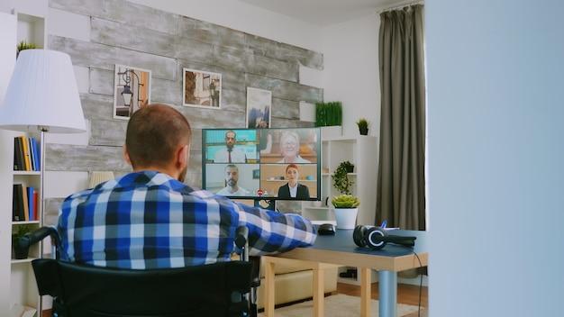 Freelancer com deficiência em cadeira de rodas durante uma chamada de vídeo a trabalhar em casa.