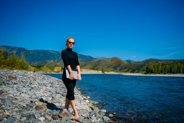 Freelancer com laptop sobre a natureza. blogger hipster viajante negócios senhora menina bonita terminou o trabalho ao ar livre. jovem mulher loira com óculos de sol em pé preto ao lado do rio da montanha