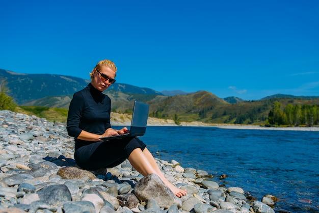 Freelancer com laptop sobre a natureza. blogger hipster viajante negócios senhora menina bonita trabalha ao ar livre. jovem mulher loira de preto sentado ao lado do rio da montanha