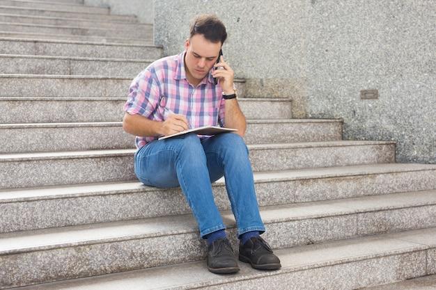Freelancer concentrado fazendo anotações e falando no telefone