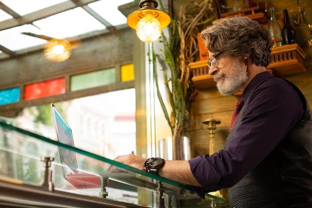 Freelancer concentrado. homem adulto sério sendo absorvido no trabalho, sentado perto da grande janela em um café.