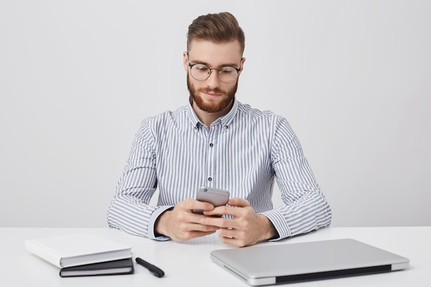 Freelancer confiante masculino repreendido com penteado da moda trabalha remotamente, olha para a tela do telefone inteligente com expressão focada, comunica-se online, desfruta de wi fi grátis no escritório, isolado na parede branca