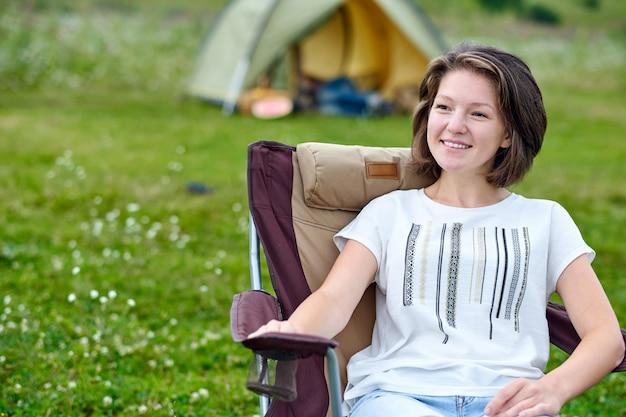 Freelancer da jovem mulher que senta-se na cadeira e que relaxa na frente da barraca no local de acampamento na floresta ou no prado.