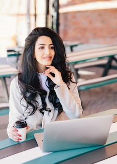 Freelancer de elegante mulher bem-sucedida vestida formalmente usando computador laptop genérico para trabalho remoto, descansando no café ao ar livre, bebendo um café delicioso com expressão de sonho. conceito de estilo de vida