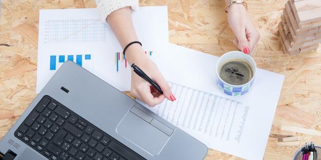 Freelancer de empresária, trabalhando na mesa em seu escritório com um laptop na vista superior