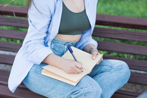 Freelancer de garota caucasiana, sentado em um banco e escrevendo em um caderno. conceito de educação e jornalismo