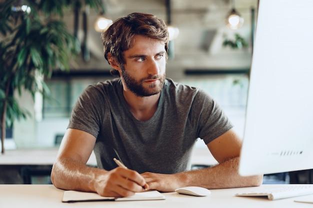 Freelancer de homem barbudo usando o computador em um moderno local de coworking