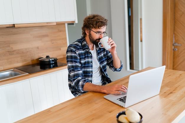 Freelancer de homem bonito usando laptop, estudando online e trabalhando em casa