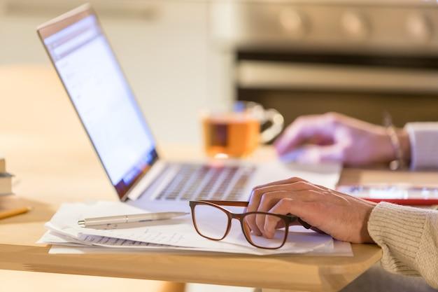 Freelancer de homem trabalhando em casa escritório no laptop, foco em óculos na mão