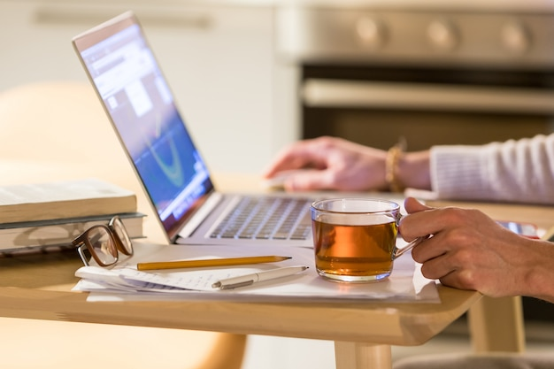 Freelancer de homem trabalhando em casa escritório no laptop, segurando uma xícara de chá