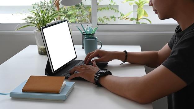 Freelancer de jovem está trabalhando em um tablet com tela em branco enquanto está sentado no escritório.