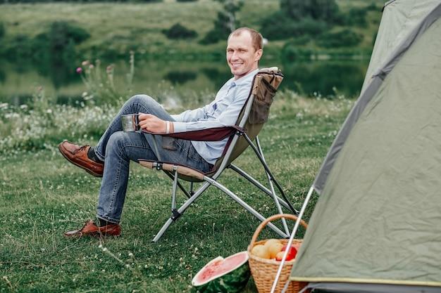 Freelancer de jovem sentado na cadeira e relaxar na frente da barraca no parque de campismo na floresta ou prado. atividade ao ar livre no verão.