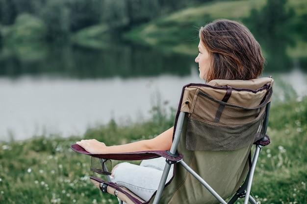 Freelancer de jovem sentado na cadeira e relaxar na natureza, perto do lago