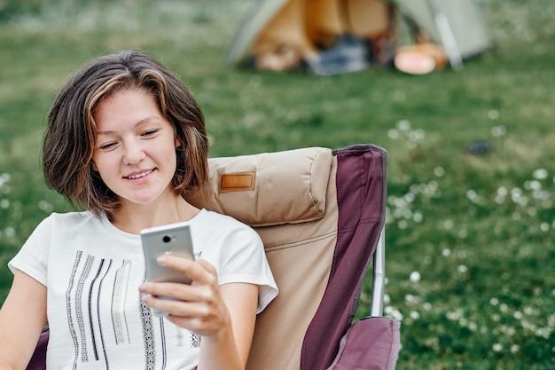 Freelancer de jovem sentado na cadeira e usando o smartphone