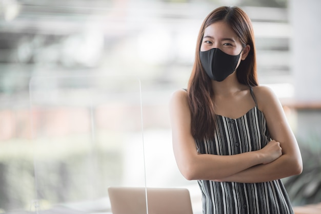 Freelancer de mulher de negócios asiática usando máscara cirúrgica, distanciamento social do novo estilo de vida normal após epidemia de coronavírus covid-19