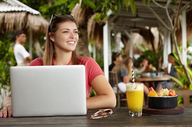 Freelancer de mulher jovem e bonita vestida casualmente, usando um laptop genérico para trabalho remoto, descansando em um restaurante ao ar livre