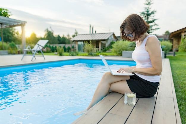 Freelancer de mulher usa um laptop sentado à beira da piscina