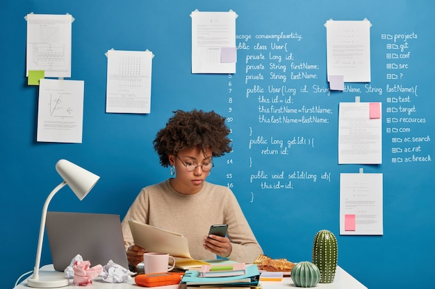 Freelancer de pele escura concentrado segura documentos em papel e telefone celular, trabalha remotamente em um espaço de coworking, assiste a webinar digital online, pensa no plano da organização