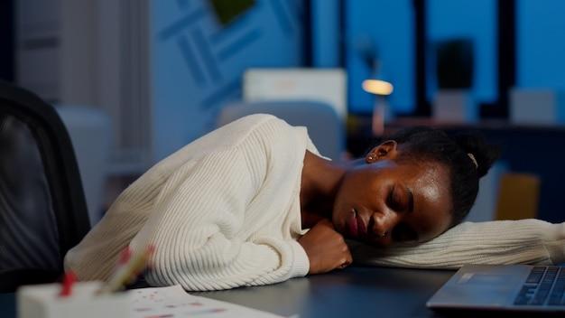 Freelancer de pele escura trabalhando horas extras adormecendo com a mão na mesa