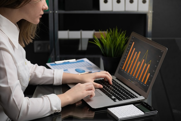 Freelancer digitando no laptop com tela preta em branco próximos gráficos e calculadora