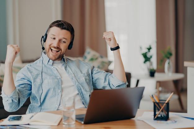 Freelancer do sexo masculino muito feliz em roupas casuais sentindo-se animado e comemorando o triunfo após uma entrevista de emprego bem-sucedida online, usando fone de ouvido com microfone e sentado em seu local de trabalho em casa