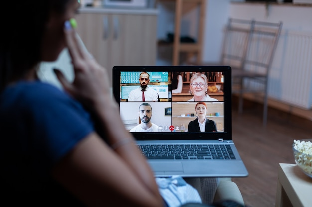 Freelancer em videoconferência à noite com a equipe sentada no sofá usando um laptop