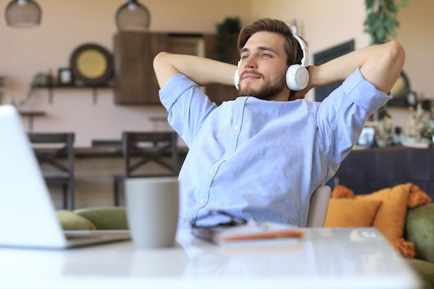 Freelancer empresário sorridente em fones de ouvido, recostado na cadeira com as mãos atrás da cabeça e sonhando com novas oportunidades de negócios.