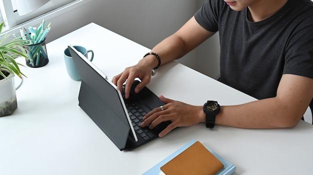 Freelancer está trabalhando em um tablet de computador enquanto está sentado em casa.