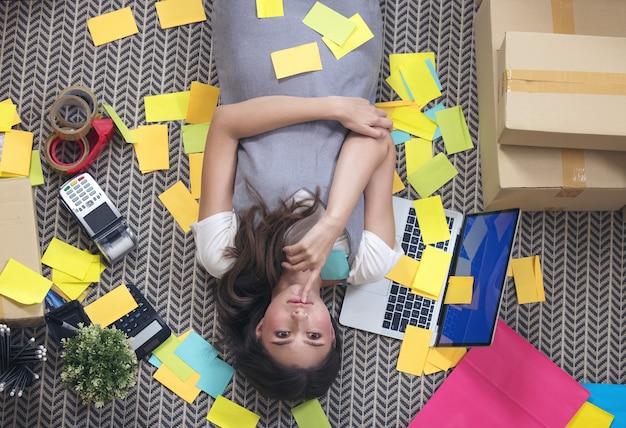 Freelancer exausto, tirando uma soneca dormindo no chão do escritório em casa. mulher atraente em casa